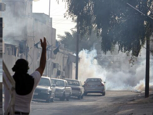 A Bahraini youth gestures as tear gas billows from a home and in the street Friday in Malkiya, Bahrain. By Hasan Jamali, AP