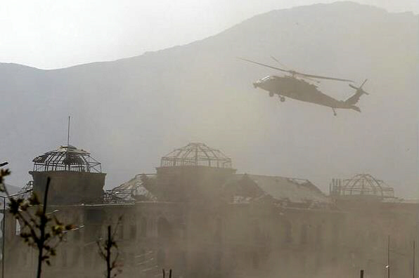 A NATO helicopter flies over the site of the attack
