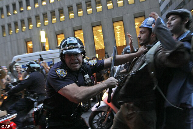 A New York City police officer shoves a demonstrator affiliated with the Occupy Wall Street protests as they march through the streets in the Wall Street area on Friday