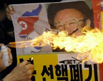 A South Korean protester burns a photo of North Korean leader Kim Jong Il