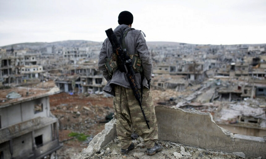 A Syrian Kurdish sniper looks at the rubble of Kobani