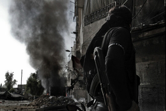 A Syrian rebel fighter looks at smoke billowing from a bus