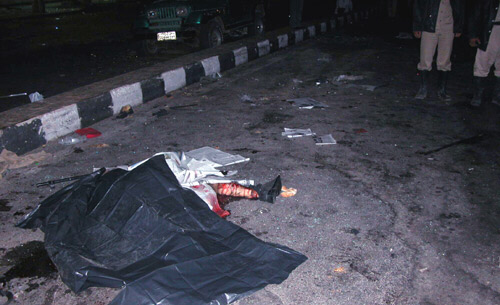 A woman's body lies amid debris on the bloody ground