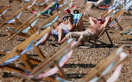 A couple enjoy the sunshine on Brighton beach, East Sussex