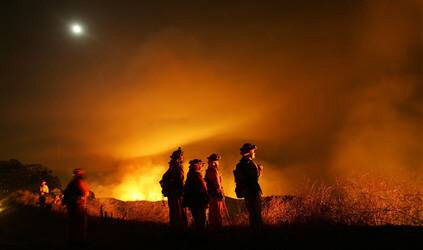 A crew prepares to cut a fireline in the early morning hours near Redlands, Calif. on Saturday.