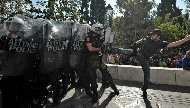 A demonstrator clashes with Greek riot police in Athens