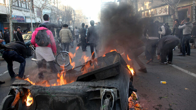 A garbage container is set on fire as Iranians protest