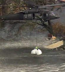 A helicopter drops sandbags during efforts to repair a broken levee