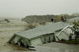 A house sits in the Santa Clara River after collapsing from floodwaters, Jan. 10, 2005: Santa Clarita, California.