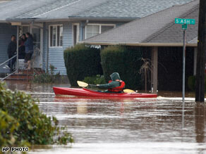 A kayaker paddles through a flooded neighborhood