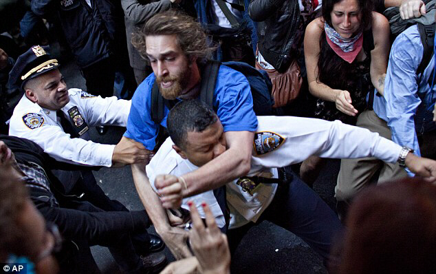 A man affiliated with the Occupy Wall Street protests tackles a police officer during a march towards Wall Street on Friday after the demonstrators were told they can stay at Zuccotti Park