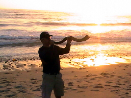 A man blows a shofar trumpet at sunset