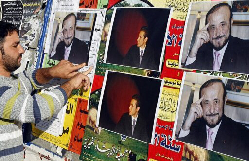 A man pastes pictures of Syrian opposition leader Rifaat al-Assad