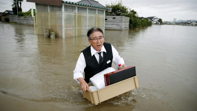 A man wades through a flooded street in Oyama, Japan