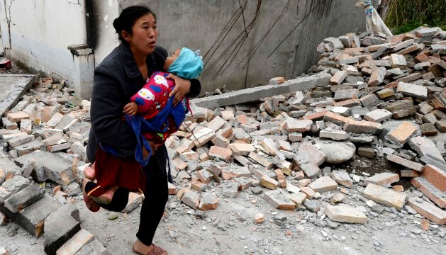A mother carries her baby through rubble in Sichuan, China