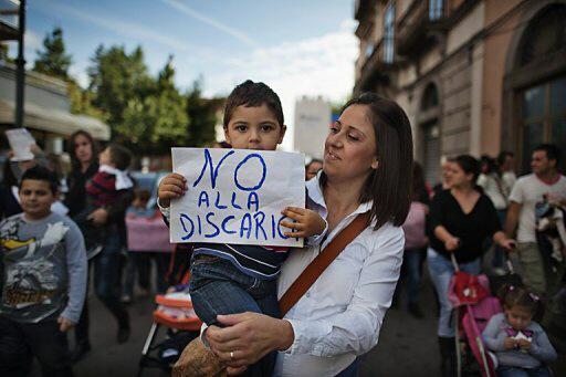 "A mother with her son, who holds a banner reading ""No to the dump"" takes part to a rally in Boscoreale"