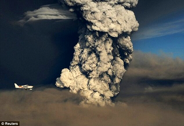 A plane flies past smoke plume from the eruption
