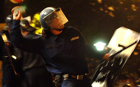 A police officer throws a stone back at demonstrators