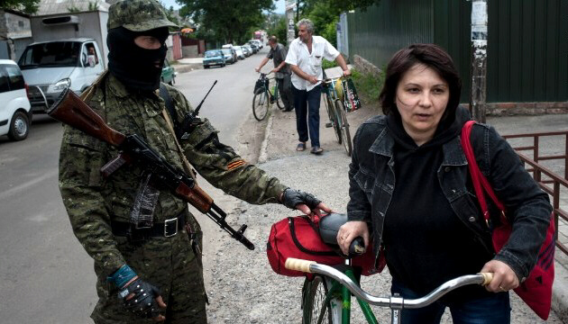 A pro-Russian fighter in Slovyansk, Ukraine, checks a woman's documents