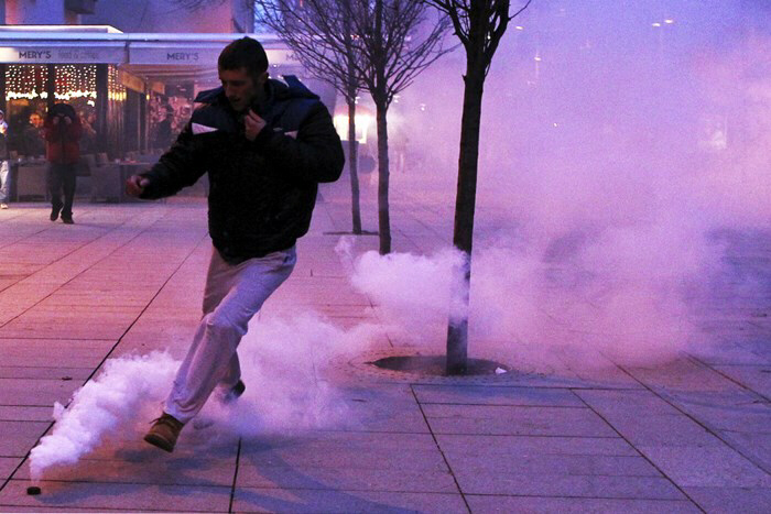 A protester kicks a tear gas canister during protest in Pristina