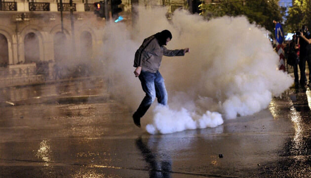 A protester kicks away tear gas canister during demonstration in Athens