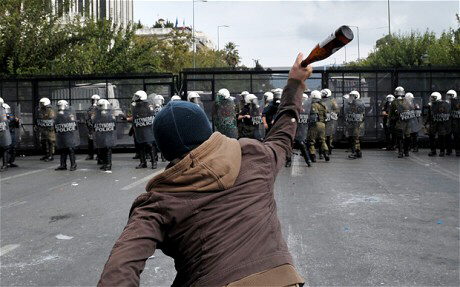 A protester throws a bottle at riot police [AFP-Getty]