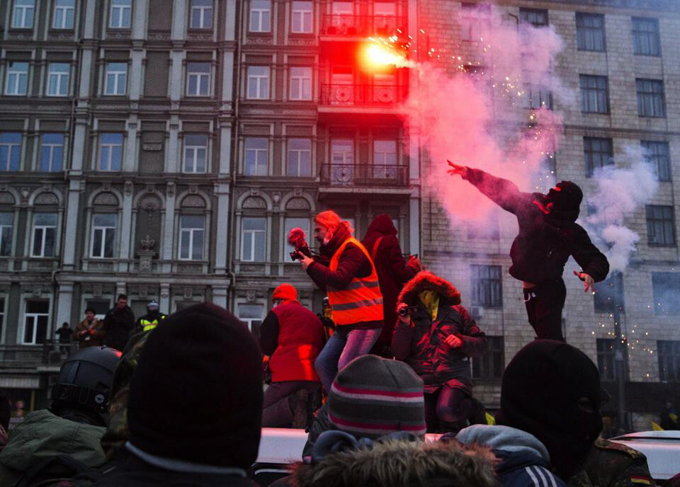 A protester throws a burning flare in Kiev