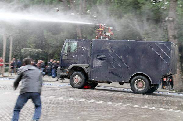 A protester throws stones at a water cannon in Tirana, Albania