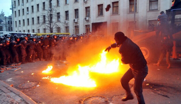 A protester throws stones toward riot police on December 1