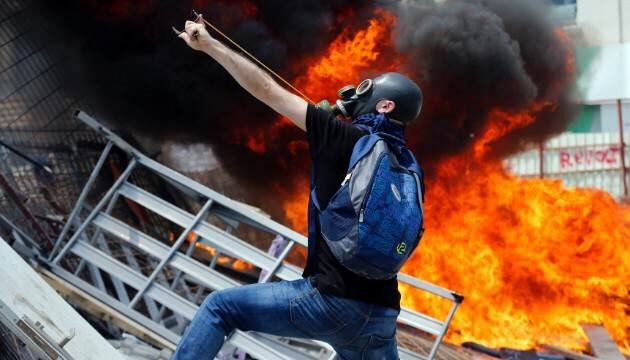 A protester uses a slingshot to throw stones at riot police