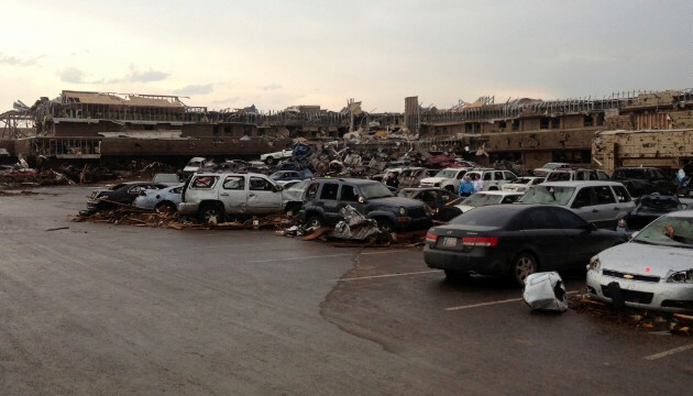 A shopping center parking lot is covered with debris and damaged cars