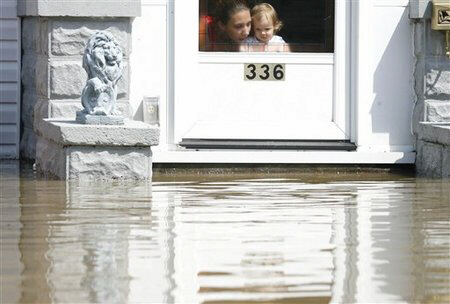 A woman and a child look out at floodwaters approaching their door Wednesday, Aug. 22, 2007, following heavy rains that caused flooding in Findlay, Ohio. Flooding remained a problem Wednesday in parts of northern Ohio, keeping streets closed, schools shut down and residents waiting things out in shelters. (AP Photo/Madalyn Ruggiero)