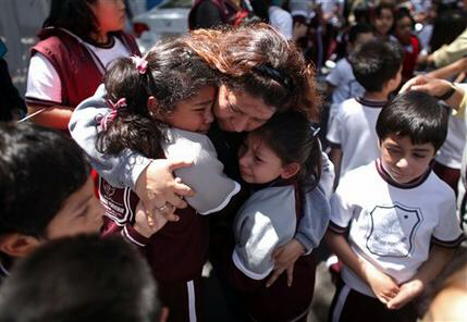 A woman comforts her children after an earthquake felt in Mexico City