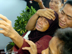 A woman grieves after learning her son is one of the victims in the Indonesian ferry accident.
