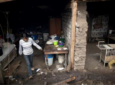 A woman leaves her damaged house after an earthquake in Cuilapa, Guatemala, Monday.