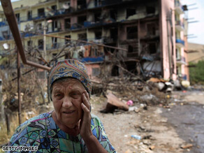 A woman outside a bombed apartment block in Gori