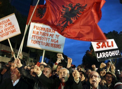 Albanians shout slogans during a protest in Tirana