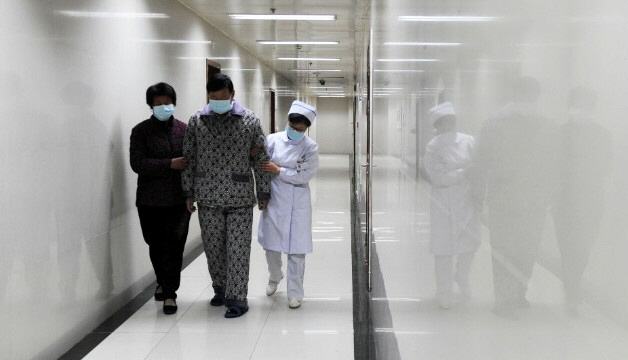 An H7N9 bird flu patient walks in corridor of hospital