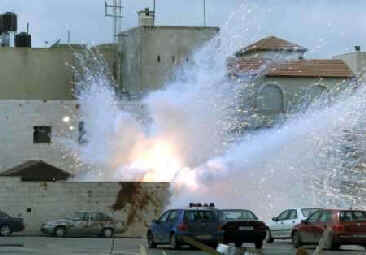 An Israeli tank shell explodes inside the headquarters of Palestinian President Yasser Arafat