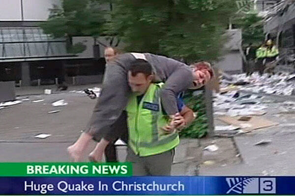 An injured woman is carried to safety in Christchurch NZ