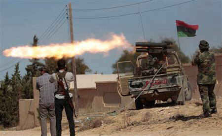 Anti-Gaddafi fighters fire a rocket during clashes with pro-Gaddafi forces