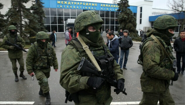 Armed men patrol Simferopol International Airport in Crimea