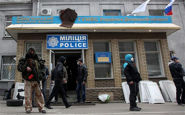 Armed pro-Russian activists guard a police station in Slavyansk