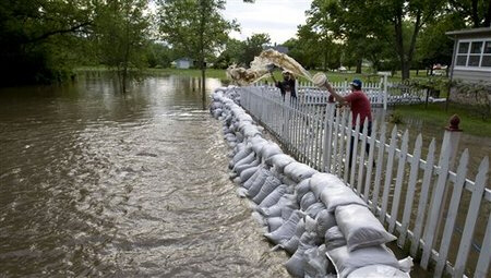 Nate Bauer, left, and Dallas Simmons help bail out flood waters from a neighboor's home along the Baraboo River Monday, June 9, 2008, in Baraboo, Wis. (AP Photo/Andy Manis)