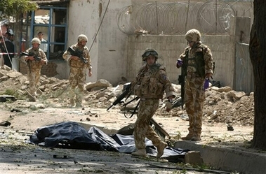 British soldiers pass by dead bodies after bomb blast in Kabul