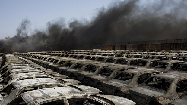 Burned cars are seen next a plume of black smoke in the port of Misrata, Libya, on Wednesday, following a fierce bombardment by government forces. (Bernat Armangue/Associated Press