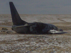 The charred, smoking wreck of Continental Flight 1404 sits on the runway