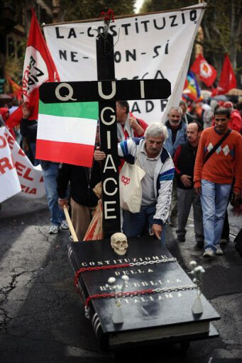 Demonstrators carry a tomb symbolising the Italian constitution during a protest in defence of labour contracts