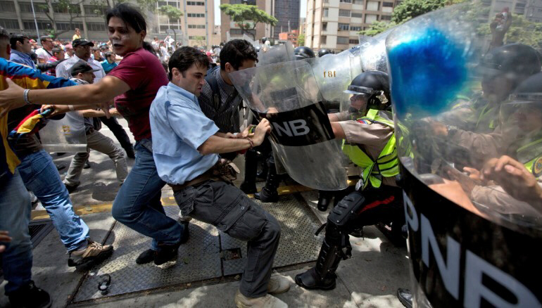 Demonstrators fight with national police officers in Caracas