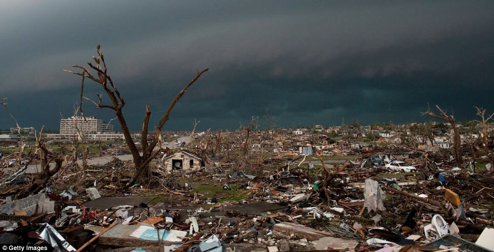 Devastation: Destroyed homes and debris cover the ground as a second storm moves in on Monday in Joplin, Missouri